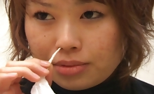 Japanese lady blows her nose onto a bunch of Kleenex tissues