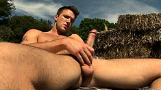 Sexy stud Sur Le Ranch strokes his stick, sitting on a stack of hay outdoors